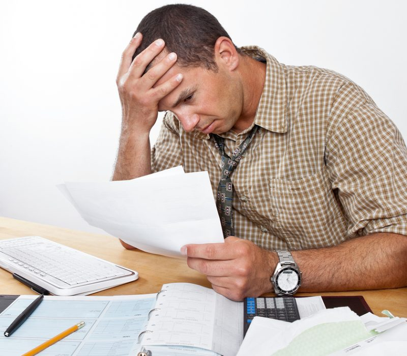 Worried exhausted young man sits at desk paying bills head in hands.